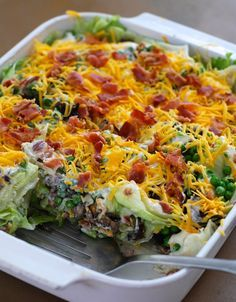 Layered salad in a cake pan: 1 head iceberg lettuce; 1/4 cup chopped purple onion; 1/2 cup chopped celery; 1/2 cup chopped green pepper; 1/2 cup chopped fresh mushrooms; 12 oz. package frozen peas thawed; 2 cups real mayonnaise; 2 Tablespoons sugar or honey; 1/4 lb. grated cheddar cheese; 1 lb. lower-sodium bacon; fried, cooled and crumbled