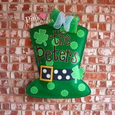 St. Patrick's Day Polka Dot Leprechaun Hat with Four Leaf Clovers and Family Name Door Hanger by Pink Brushstrokes