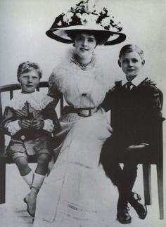 1910 Princess Daisy of Pless with children Hansel and Lexel   Princess Daisy poses in a dress with a frilly top under a wide flower-bedecked hat. She wears whar appears to be an A-line skirt secured by a belt.