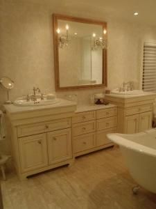 Put a dresser between the vanities, but I'd like a taller one and two individual mirrors.