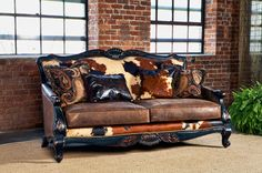 Western style leather love seat with old world styling, leather & damask print cushions