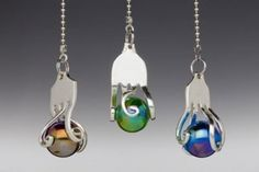 The fan pull is made from the tine end of a fork. It has been heated and gently twisted around an iridescent marble. Colors available are clear, amber, aqua, e