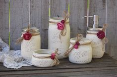Rustic mason jar bathroom jar set. Hand painted in ivory, lightly distressed, tied with jute and roses in shades of orchid and rose, finished with a protective coating. Metal soap dispenser, toothbrus