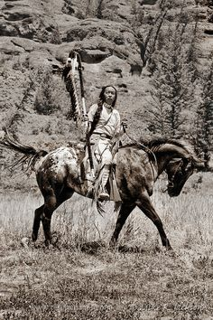 Mounted Warrior - Cherokee Native American Indian in traditional costume against rock cliffs in western Wyoming. © Mike R. Jackson