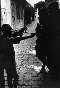A young boy playing his violin for his play-mates in the slums where the gypsies live, Hungary, 1937