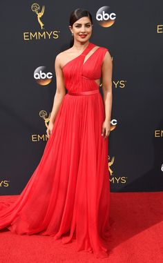 2016 Emmys: Priyanka Chopra is wearing a red silk chiffon one shoulder Jason Wu gown with cutouts. Red hot glamorous! The dress fits her like a glove. The dress flows beautifully on the red carpet!