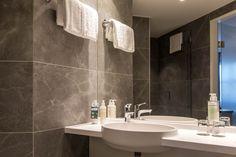 Für die Bäder hat die Hoteleigentümerin bei SCHUBERT STONE über 4000m2 von einem edlen, grauen Technostein in Natursteinoptik in der Plattengröße 45x90x1cm ausgewählt. Der hochwertige Stein passt besonders gut zur Einrichtung der Zimmer. Techno, Bad, Bathroom Lighting, Mirror, Furniture, Home Decor, Porcelain Tiles, Stones, Bathroom Light Fittings