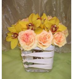 Gold cymbidium orchids & peach roses in oval vase with white ribbon