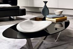 An organic, sensual table design that is perfect for creating an elegant feel within the home. Black or bronze mirrored glass top or toughened glass white lacquered on the reverse side or canaletto walnut veneer top.  Dimensions: 180 x 86 x H20cm