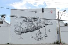 """Liqen's contribution to Wall Therapy in Rochester, NY is a provocative black and white mural with strong line work. The image consists of an American eagle captured, guarded and under surveillance, likely a metaphor for American's """"freedoms."""""""