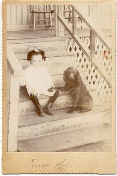 Girl holding paw of her dog on stairs.1897.