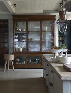 Apothecary style kitchen cabinet, vintage industrial. I really like how they left the back of the cabinet open so that you can see the shimmery subway tile through the wavy glass.
