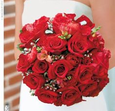Julia carried a bouquet composed mostly of red roses, red ranunculus, and red freesia, tied together with a platinum ribbon.