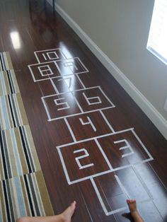 Masking tape hopscotch in living room!  This is an easy-peasy project for any day that is too hot, too cold, too windy, or too rainy to play outside.  Could make on a mat for easy storage and setup?