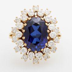 Damenring besetzt mit einem ovalfac., blauen Stein (ca. 13,5 x 9,8mm) zweifach entouriert mit kleine