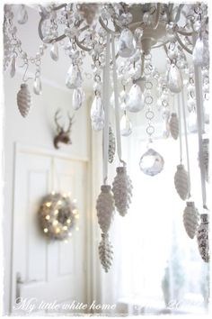 Christmas ornaments on chandelier. White, silver and gold.