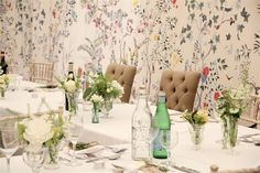 Collection of vintage glass vases and bottles lining the length of the tables and filled with a selection of delicate summer flowers