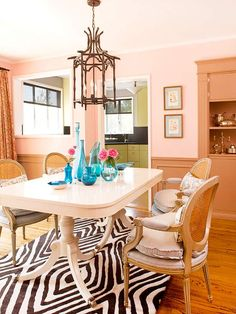 pastel pink can be a sophisticated base for an adult color scheme. in this dining room, pink flirts w coral tones for a rich color that looks even deeper in the evening. geometric black and white rug adds a contemporary note underfoot Decor, Furniture, Home Decor Inspiration, House Design, Room, Interior, Home Decor, Interior Design, Pink Dining Rooms