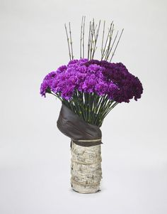Light and dark purple carnations set against black dogwood and framed with black cordyline leaves in a birch-wrapped vase