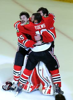 Chicago Blackhawks center Andrew Shaw, Chicago Blackhawks center Jonathan Toews celebrate with Chicago Blackhawks goalie Corey Crawford hoists the cup after winning the Stanley Cup Monday night at the United Center in Chicago.