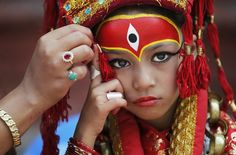 A Nepalese mother applies make up to her daughter dressed as the living goddess Kumari as they wait for Kumari puja to start at Hanuman Dhoka temple, in Kathmandu, Nepal, Wednesday, Sept. 14, 2016. Girls under the age of nine gathered for the Kumari puja, a tradition of worshiping young prepubescent girls as manifestations of the divine female energy. The ritual holds a strong religious significance in the Newar community that seeks divine blessings to save small girls from diseases
