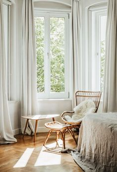 Serene bedroom in pale and neutral shades | rattan chair and footstool | linen bedspread | cream off white curtains | did you know that Bemz offers custom curtains in all our 250+ fabrics | Get the look with Bemz curtains in Eggshell Zaragoza Vintage Velvet by Designers Guild