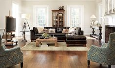 Living room with brown leather sectional, hardwood floors, light and airy, feminine