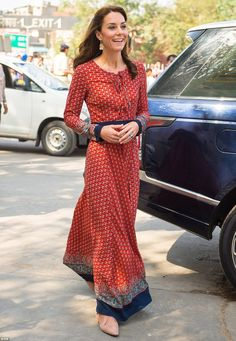 Relaxed: Kate wore flat cream pumps underneath a long burgundy ethnic style dress with a b...