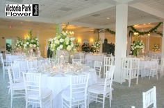 Beautifully tall centerpieces designed with White Hydrangea, Stock and Roses with Green Dianthus, Fuji Mums, Bells of Ireland and Curly Willow and Garlands to Match