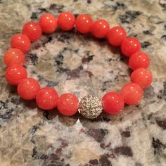 """Coral and crystal pave bead bracelet Coral and crystal pave bead bracelet // stretchy // never been worn // beads measure 10 mm and crystal 10 mm // bracelet measures 7"""" but will stretch larger // great quality & condition // cute by itself or add to an arm party Jewelry Bracelets"""