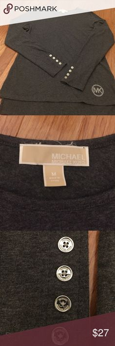 """Michael Kors Long Sleeve Top w/ Bling MK Logo Charcoal grey long sleeve Michael Kors top. 95%cotton 5%elastane gives it a comfy fit!. Each sleeve has 4 small """"Michael Kors"""" buttons . Top has slight hi/lo. Lower left front has small Studded logo that give this top its bling. Excellent condition...wore 1 time. Buttons and bling are silver tone. Michael Kors Tops Tees - Long Sleeve"""