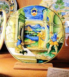 Chateau-Ecouen- Pâris tuant Achille. D'après les Métamorphoses d'Ovide; armoiries des LEONARDI DE PESARO. Urbino, NICOLA DA URBINO, vers 1525. Faïence (terre cuite, émail stannifère)- Acq 1997. EC.278. Assiette du service Leonardi, famille de Pesaro, représentant le Mort d'Achille.