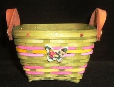 """Made with Maple, our 2020 Spring Forth Basket is Sage Green with Pink and Yellow accent weave, leather handles and an adorable  """"Spring"""" tie-on!   NOTE: Tie-on's may differ with each basket.   Measures 3.25"""" x 3.25"""" at the top and is 2 1/8"""" tall  (measurements may vary and do not include leather handles).   $30.00     $30.00 Yellow Accents, Leather Handle, Sage, Baskets, Weaving, Miniatures, Spring, Green, Crafts"""