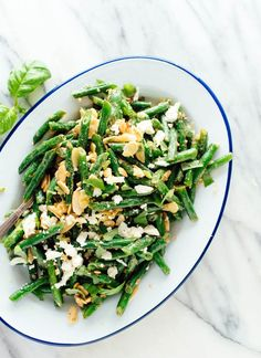 This green bean salad is the best! Perfectly cooked green beans tossed in a lemony dressing with toasted almonds, feta and basil. Learn how to make it here!