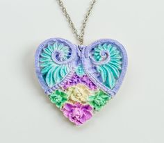 This gorgeous heart necklace with flowers and wings is fully handcrafted. Its made of polymer clay and silver toned chain.  The length is 28 cm