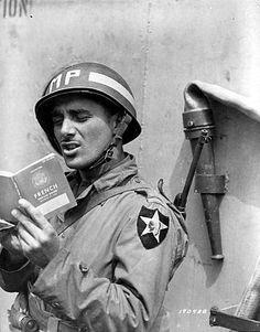 Le 15 juin 1944, le Pfc Rocco Festa membre de la Military Police de la 2nd Infantry Division, à bord d'un navire en route pour la Normandie s'exerce au Français, grâce à son french book.
