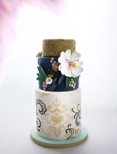 TYRION | Charm City Cakes Summer 2013 Collection. Large bottom tier is white with gold and black patterns, followed by the teal middle tier covered in gorgeous flowers, and topped with a gold final tier.