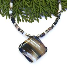 This beautiful gemstone necklace was named GANYMEDE after looking at photos of the largest moon orbiting Jupiter. The black, white and taupe stripes of the banded black agate perfectly mimic many pictures of the of the moon taken by NASA.