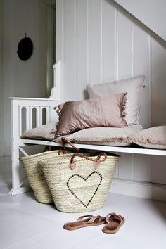 Wit houten bankje bevestigd aan wand, met mooie accessoires.
