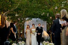 Bride walking down aisle at the Four Seasons. This canopy of trees decorated with tea lights in glass globes gives a really elegant look to this aisle / The Four Seasons Miami FL wedding of Jessica & Josh / Photo by Maloman Studios
