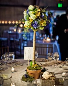 Tall centerpieces give a natural and rustic feel to an elegant wedding | Photo by JAGstudios