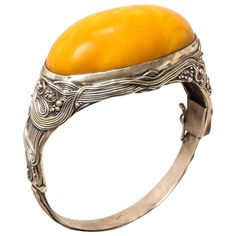 Austrian Art Nouveau Cabochon Amber Silver Bangle Bracelet. The bangle is set with a large cabochon-shaped amber stone in beautiful warm butterscotch shade. It is decorated with small intricately entwined lines which run all the way around and are enhanced by tiny berries or pearls. It has a v-shaped clasp which functions perfectly, and a small safety link. c 1910