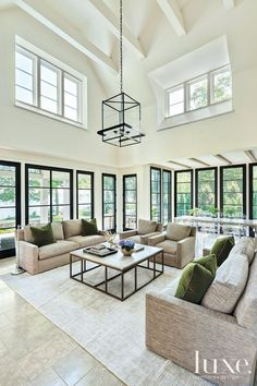 Abundant windows frame the views in the family room and allow the outdoors in. A. Rudin sofas and chairs topped with durable dyed acrylic fabrics from Holly Hunt and the custom-size Tavolino wood-and-iron coffee table by Formations create the focal points.