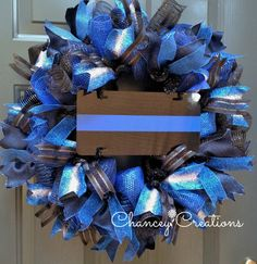 Show your support for Law Enforcement with this Thin Blue Line Wreath. Constructed on a wire wreath frame with four different patterns of Poly Deco Mesh: Metallic Navy/Royal, Metallic Black, Deluxe Wide Foil Royal Blue and Deluxe Wide Foil Metallic Black. Four different coordinating patters of wire ribbon are layered throughout this handcrafted wreath. A high gloss, aluminum, Thin Blue Line sign is positioned at the center.  They answer our cries for help without a second thought. Let's ...