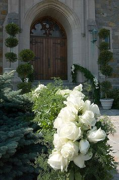 Topiaries and railings decorated with greens and white  roses lead guests to the entrance of the church.