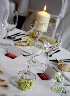 Sviečka so saténovou stuhou na dekoračnom svietniku s ružami.
