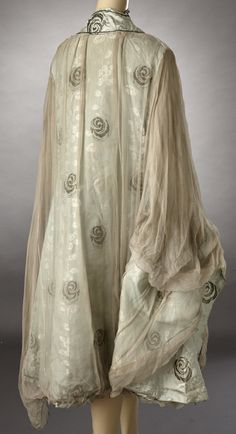 1910s late teens probably after WWI which would be the Armistice era. Aqua silk brocade cape lined in silk Georgette with large ovals of silver bullion lace. This is such an unusual design I just love it! It is a shame that there are issues with the cape. Breaks in the lace and some splits forming in the brocade. Please look carefully at the photos, the damage is shown. Even with the damage I think it is a great piece for a collection. CONDITION: GOOD SIZE: ONE SIZE FITS ALL SKU (product)…