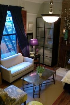 A cozy apartment living room with jewel tone touches and small furniture to fit the space.