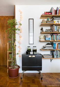 Prateleiras de madeira sustentadas por mão francesa e geladeira antiga decoram a sala de estar.