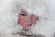 nenya vanuito, a young nenets girl, wearing a traditional hat with fur trim at a winter camp near tambey | yamal peninsula, western siberia, russia | foto: bryan & cherry alexander